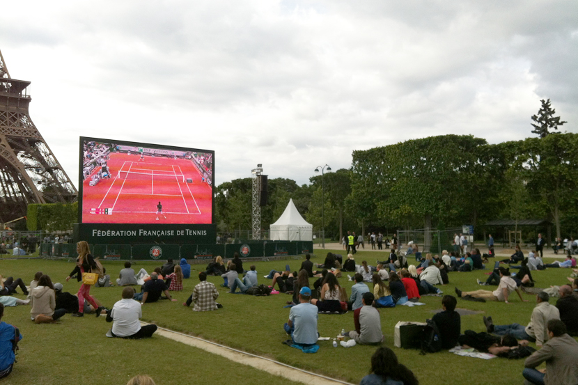 O pessoal assistindo à uma partida de Roland Garros no Champ de Mars.
