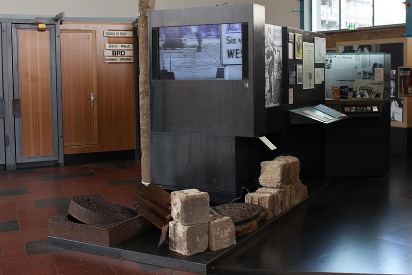 Pedações do muro, vídeos sobre a vigilância naquela época e algumas cabines originais ao fundo.