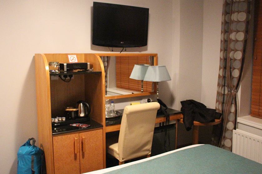 Tinha uma escrivaninha, cafeteira, chaleira e TV no quarto, em frente à cama. Bem útil.
